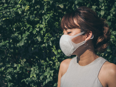 Beautiful asian woman close her eyes and wearing white protective N95 dust mask on green leaves background with copy space. Protection against pollution concept.