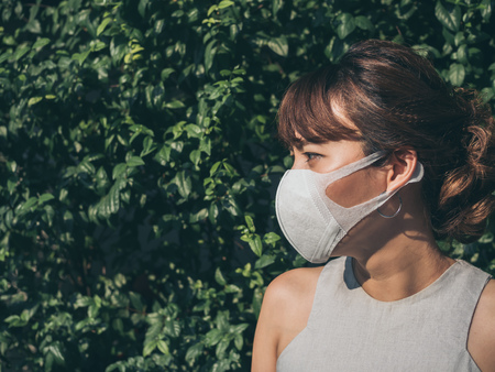 Beautiful asian woman wearing white protective N95 dust mask on green leaves background with copy space. Protection against pollution concept.