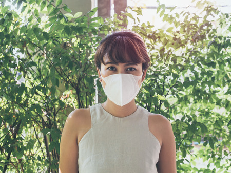 Beautiful asian woman wearing white protective N95 dust mask on green leaves background with sunlight. Protection against pollution concept. 版權商用圖片