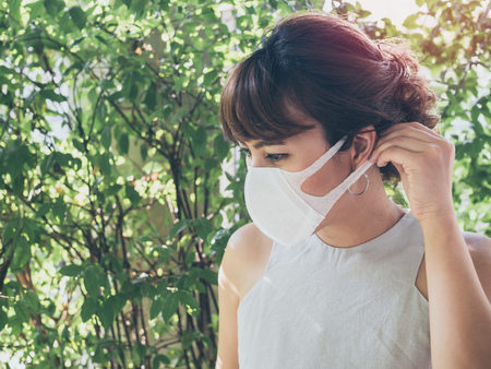 Beautiful asian woman wearing white protective N95 dust mask on green leaves background with copy space. Protection against pollution concept. 免版税图像 - 119416861