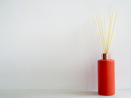 Air freshener stick in red bottle on white wall background with copy space. Aromatic reed stick in modern bottle.