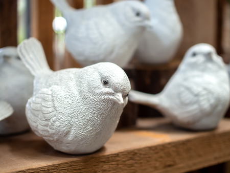 Close-up white realistic mortar bird sculpture decoration on wooden background.