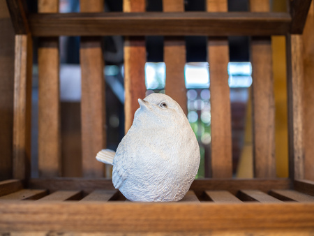White realistic mortar bird sculpture decoration on wooden background. Imagens - 119416870