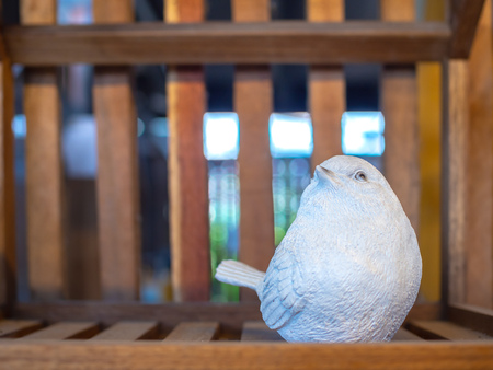 White realistic mortar bird sculpture decoration on wooden background with copy space. 版權商用圖片