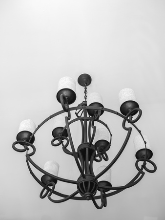 Vintage black chandelier with white candles on white ceiling background with copy space vertical style.
