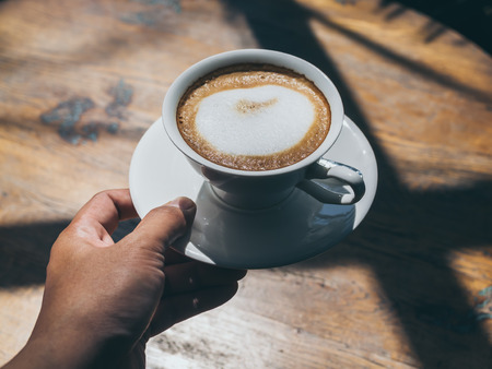 Hand holding hot coffee in round white ceramic cup with white spoon on white saucer on wooden table background with beautiful light and shadow.