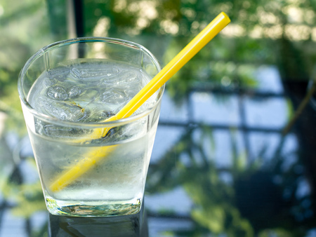 A glass of cold drinking water with ice and yellow straw on glass table with copy space.