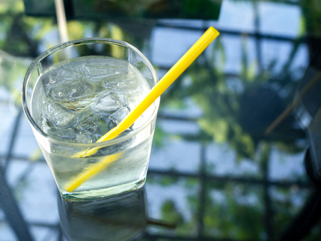 A glass of cold drinking water with ice and yellow straw on glass table with copy space on top view.