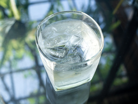 A glass of cold drinking water with ice on glass table. 版權商用圖片