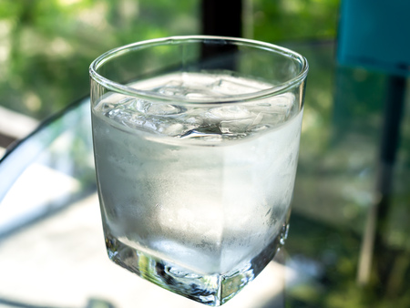 A glose up glass of cold drinking water with ice on glass table.