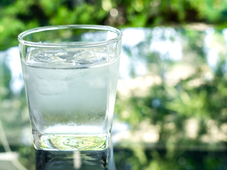 A glass of cold drinking water with ice on glass table on nature background with copy space.