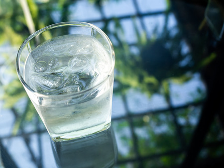 A glass of cold drinking water with ice on glass table with copy space on top view. 版權商用圖片
