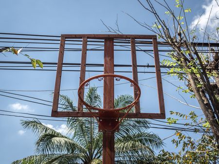 Old red basketball hoop near trees and busy electric wires on blue sky background.