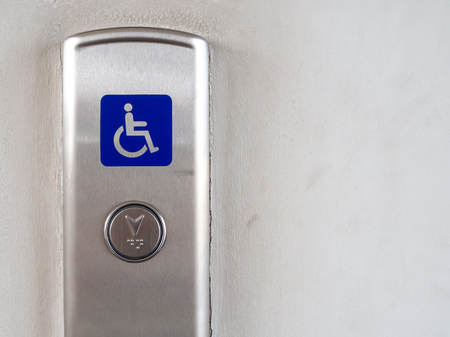 Elevator button with blue disabled people sign on stainless steel elevator panel on old and dirty white background with copy space. Elevator button for blind and disabled people.