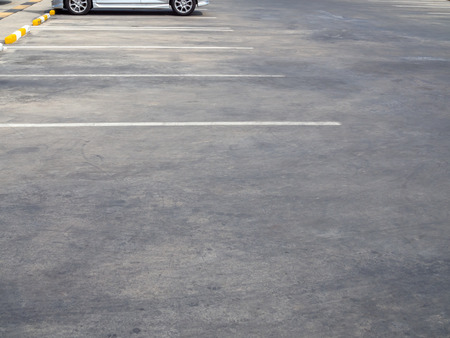 Empty old outdoor parking lot with car and white line on sunny day with copy space.