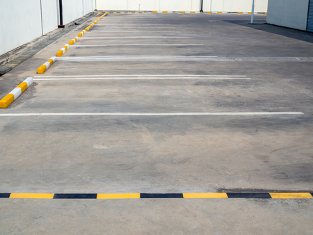 Empty old outdoor parking lot with yellow and white line near building and white wall on sunny day with copy space. 版權商用圖片