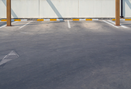 Empty old outdoor parking lot near the wall on sunny day with copy space.