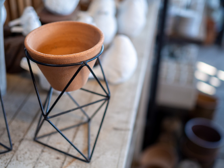 Empty small terracotta pot in modern black geometric Iron rack holder on wooden table with copy space. 版權商用圖片