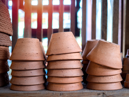 Piles of terracotta pots on old wooden shelf in local terracotta pot factory.