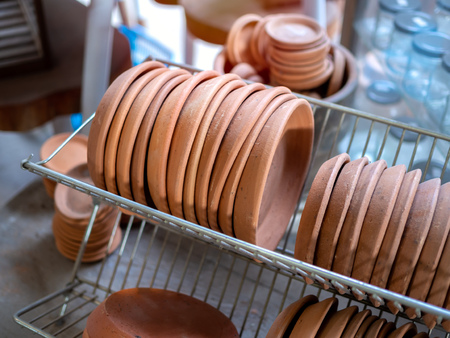 Row of terracotta dishes on old stainless steel shelf in local terracotta factory.