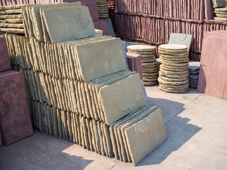 Rows and piles of square and round stone plates for garden decoration.