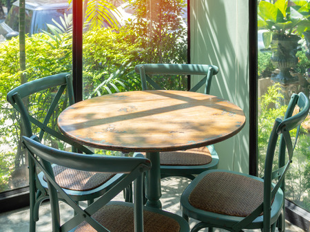 Vintage wooden table and four green chairs in the corner of restaurant with window glass near the garden.