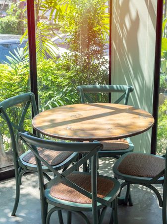 Vintage wooden table and four green chairs in the corner of restaurant with window glass near the garden in vertical style.