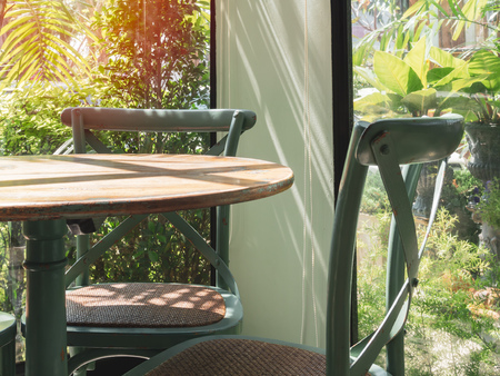 Close-up vintage wooden table and green chair in the corner of restaurant with window glass near the garden. 版權商用圖片