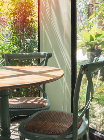 Close-up vintage wooden table and green chair in the corner of restaurant with window glass near the garden in vertical style.