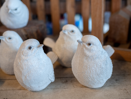 Many white realistic mortar bird sculpture decoration on wooden background. 版權商用圖片