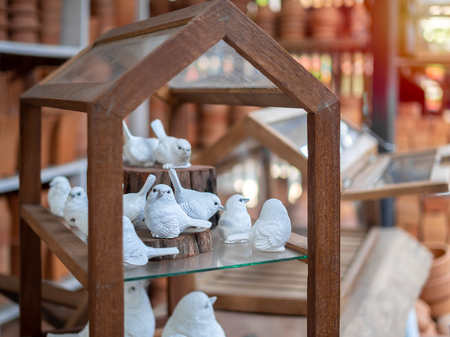 Many white realistic mortar bird sculpture decoration on wooden house. Banco de Imagens - 119416996