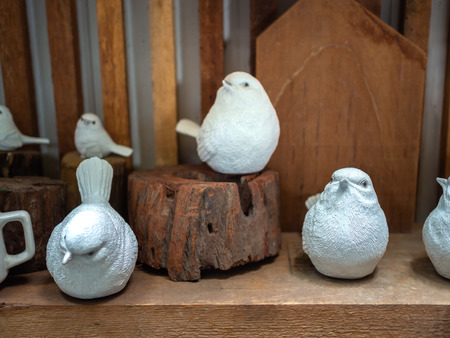 Many white realistic mortar bird sculpture decoration on wooden background. Banco de Imagens