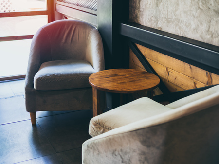 Vintage fabric armchair with round wooden table near the wall, concrete, black steel and wooden wall in cafe. Stock Photo