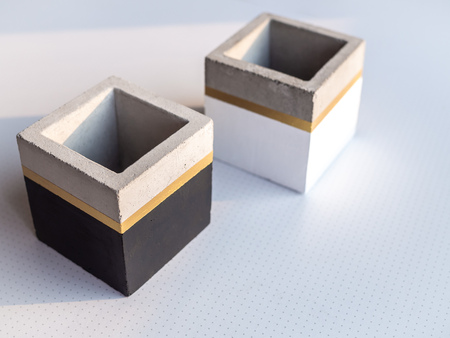 Two empty modern black and white cubic concrete planters on white background with copy space. Painted concrete pot for home decoration.