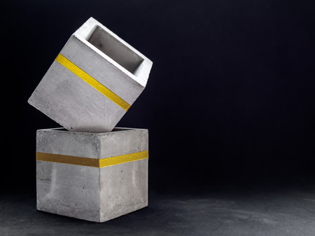 Two empty modern cubic concrete planters with gold color bar on dark background with copy space. Painted concrete pot for home decoration. Imagens