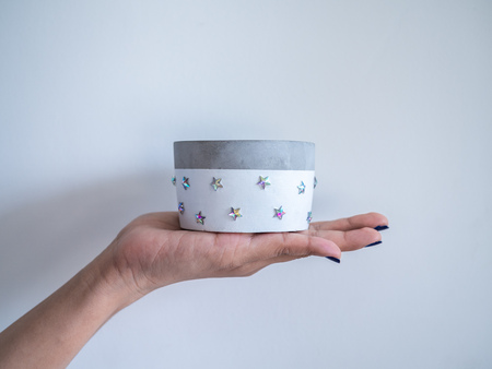 Hand showing empty white modern round concrete planter with shining star pattern on white background. Painted concrete pot for home decoration