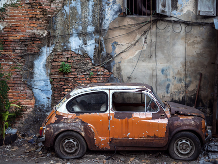 Old abandoned rusty car with flat tires on old brick wall background. Stock Photo