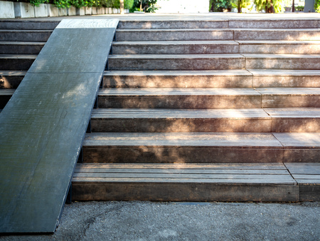 Plank wood stair outdoor with wooden wheelchair ramp. Old wooden stair with wooden slope path.