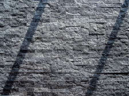 Modern grey brick wall texture background. Shadow shade light on stone brick tiles texture. Minimalist style wall background with copy space.