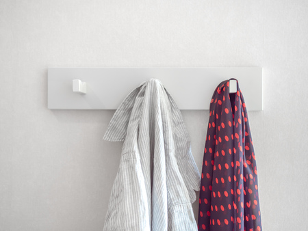 White relaxed striped shirt and red polka dot pattern scarf hanging on white modern hanger on white wall background.