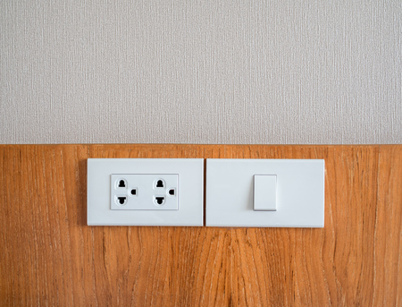 White electrical socket and white light switch on wooden and wall background with copy space.
