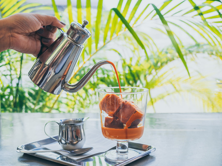 Hand pouring Thai milk tea from stainless steel jug on Thai tea ice cubes in glass with milk in small jug on stainless steel tray on concrete table. 스톡 콘텐츠 - 123826319