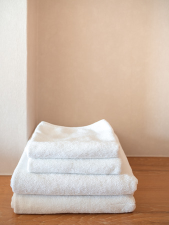 White clean towels on wooden surface and white wall background with copy space vertical style.