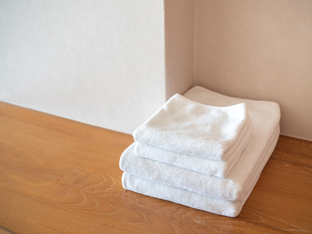 White clean towels on wooden surface and white wall background with copy space.