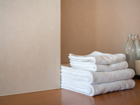 White clean towels and bottle of drinking water on wooden surface and white wall background in hotel with copy space. 版權商用圖片