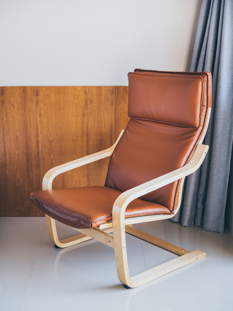 Brown leather on wooden armchair in hotel room. Modern armchair Layer-glued bent birch frame gives comfortable resilience.