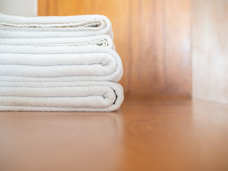 Close-up white clean towels on wooden background with copy space.