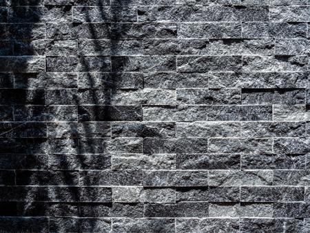Tropical palm leaf shadow on modern grey brick wall background. Grey stone brick tiles texture.