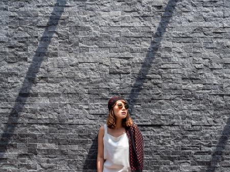 Beautiful fashionable hipster asian woman wearing white sleeveless, sunglasses and red polka dot pattern turban smiling on modern grey brick wall background minimalist style.