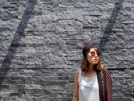 Beautiful fashionable hipster asian woman wearing white sleeveless, sunglasses and red polka dot pattern turban smiling on modern grey brick wall background with copy space.